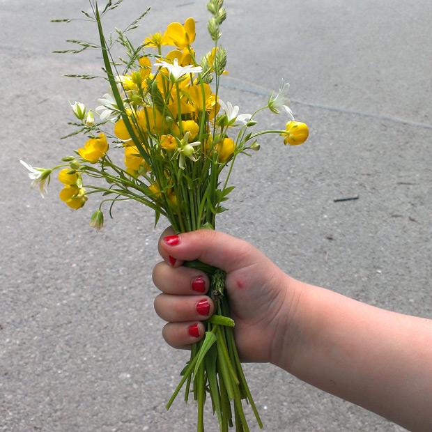 Kind 2 mit lackierten Fingernägeln und einem gepflückten Blumenstrauß